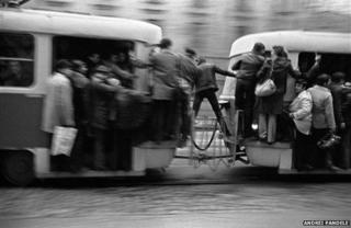 Photo of man straddling trams in Bucharest