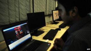 A Pakistan man chats with his friend on a online network in the port city of Karachi
