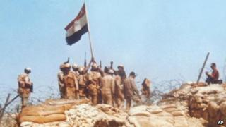 Egyptian soldiers raise a flag on Bar-Lev line bunker in Sinai, during the Middle East war of 1973