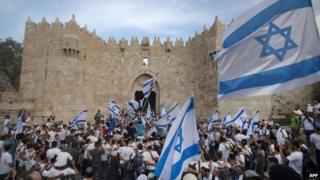 "Israeli youths hold their national flag as they take part in the ""flag march"" through Damascus Gate in Jerusalem's old city during celebrations for Jerusalem Day on 8 May, 2013."
