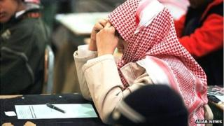 A Saudi student holds his hands to his head