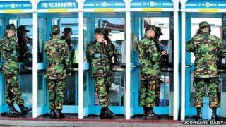Soldiers using phone boxes in Seoul
