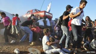 People run as an out-of-control monster truck ploughs through a crowd of spectators at a Mexican air show in the city of Chihuahua on 5 October 2013