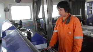 A man in an orange boiler suit on the bridge of a large ship