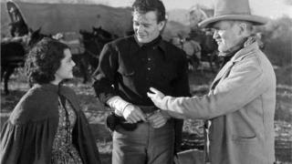 John Wayne standing between two people in The Oregon Trail