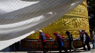 Tourists and locals turn a prayer wheel in Shangri-La country in the southern Yunnan province of China