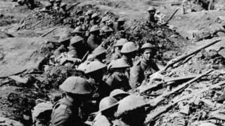 British infantrymen occupying a shallow trench in a ruined landscape