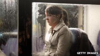 A picture of a woman on a bus in the rain