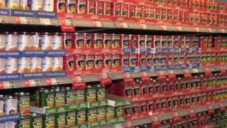 Tinned food on supermarket shelf.
