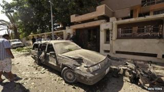 People look at a damaged car outside the Swedish consulate after a car bomb explosion, in Benghazi on 11 October 2013.