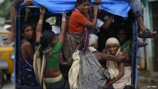 Villagers in an auto rickshaw return to their villages after Cyclone Phailin hit Girisola town in Ganjam district in the eastern Indian state of Orissa on October 13, 2013