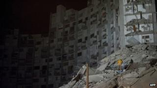 Colombian firefighters search for survivors in the debris after a building collapsed in Medellin on 12 October, 2013