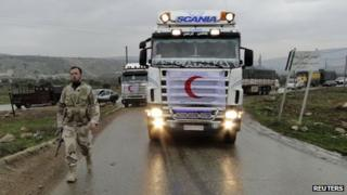 A Free Syrian Army fighter walks in front of a convoy carrying humanitarian aid from the Syrian Arab Red Crescent in Deir Semaan in Aleppo's countryside (file photo)