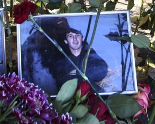 Flowers surround a portrait of Yegor Shcherbakov, 25, who was stabbed to death in a dispute over his girlfriend with another man as the couple returned home in Moscow, 10 October