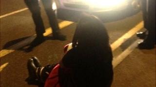 the woman sits in front of police officers
