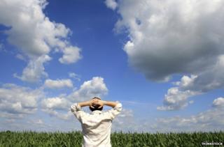 Man with hands behind head, staring at horizon
