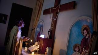 A Syrian Christian priest prays at Mar Elias House, a church hostel for the elderly in Aleppo (20 September 2013)