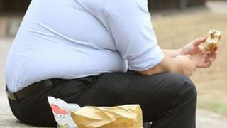 Obese man eating burger