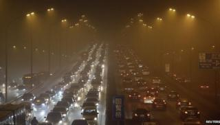 Vehicles drive on the Third Ring Road on a very hazy winter day in Beijing