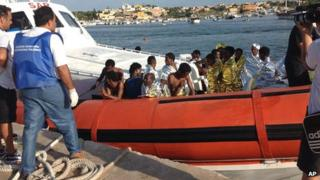 An Italian Coast Guard boat carry rescued migrants as they arrive in the port of Lampedusa on 3 October 2013