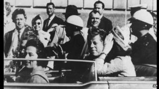 JFK, in Dallas on November 23rd 1963. JFK is seen in the back of the car as it passes close to the book depository, where Lee Harvey Oswald (the alleged assassin)