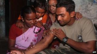 Indian police commando, Ganesh Raghunath Dhangade (R), shows a tattoo to his family in Thane district on the outskirts of Mumbai on October 16, 2013.