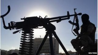 A member of the Libyan Army special forces who took military action against a militia group that took over public land, holds his weapon, in Benghazi October 3