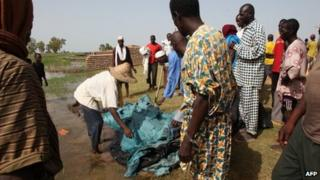 People stand near the covered body of a person who died in the sinking of a river boat on the River Niger