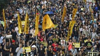 Protesters, many wearing black clothes, march on a Hong Kong street Sunday, Oct. 20, 2013