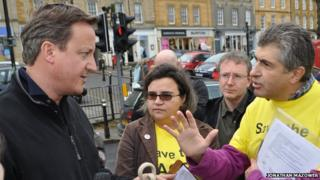 David Cameron in Chipping Norton being confronted by ACE Centre protesters