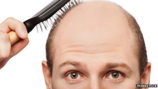 Bald man combing scalp