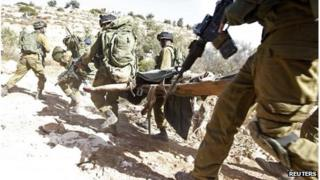 Israeli troops carry Mohammad Assi on stretcher (22/10/13)