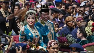 Gusti Kanjeng Ratu Hayu and KPH Notonegoro wave to crowds while on their journey by carriage during the wedding ceremony parade.