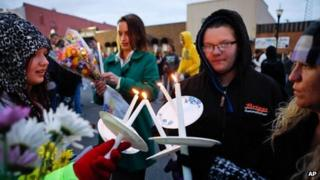 "Sarah Linthacum, right, Maggie Baker, second from right, and Gabrielle Stewart, left, try to keep their candles lit despite the wind during the ""Justice for Daisy"" rally in Maryville, Missouri 22 October 2013"