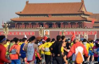 Participants run through Tiananmen Square, with the Forbidden City in the background