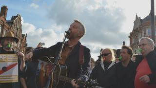 Billy Bragg singing with Bill Bailey and Mark Thomas playing the kazoo