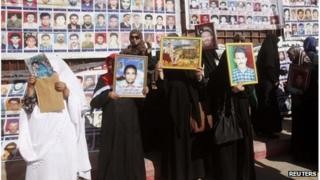 Relatives hold portraits of prisoners who died during the 1996 Abu Salim Prison massacre, as they protest outside the appeals court in Tripoli, 24 October, 2013.