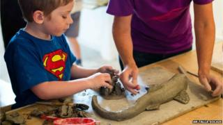 Boy working on clay fish for new sculpture