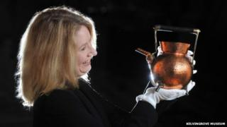 Curator Alison Brown with copper kettle designed by Christopher Dresser