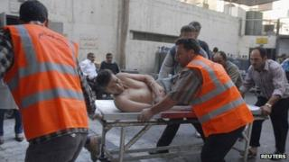 Emergency crews help a car bomb victim in Damascus province in this handout photo provided to Reuters by Syrian state news agency SANA