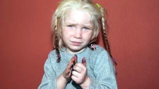 Blonde haired girl facing camera