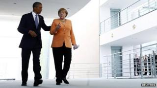 US President Barack Obama and German Chancellor Angela Merkel (R) making their way to a news conference at the Chancellery in Berlin (19 June 2013)