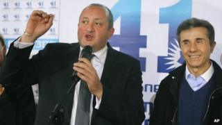 Georgia's Prime Minister Bidzina Ivanishvili, right, and presidential candidate Giorgi Margvelashvili, left, greet supporters at the Georgian Dream coalition headquarters in Tbilisi, Georgia (27 Oct. 2013)