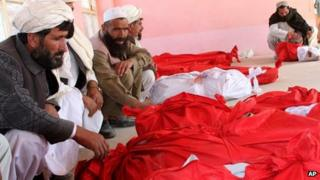 Relatives surround the shrouded bodies of the victims of Sunday's blast