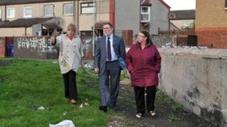 Social Development Minister, Nelson McCausland is shown a derelict area of west Belfast.