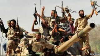 Anti-Gaddafi fighters celebrate the fall of Sirte in the town on 20 October, 2011. Libyan rebel fighters seated in tank with guns raised in air