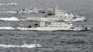 A Japanese fishing boat, bottom, a small Japanese pleasure boat, top centre, Japan Coast Guard vessels, third and fourth from bottom and top left, sail along with a Chinese surveillance ship near disputed islands called Senkaku in Japan and Diaoyu in China in the East China Sea, 23 April 2013