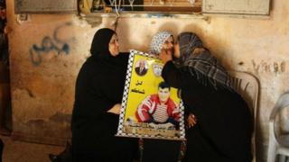 A relative of Palestinian prisoner Omar Masood kisses his mother (C) as they react after hearing news of Omar's expected release by Israel