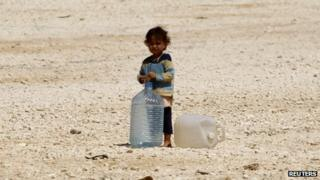 A young Syrian refugee stands beside water containers at the Zaatari refugee camp in the Jordanian city of Mafraq