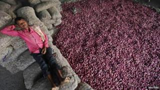 A labourer rests on sacks filled with onions at a wholesale vegetable market in the northern Indian city of Chandigarh on 24 October 2013